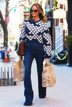 Chrissy Teigen in a printed crew neck sweater paired with flared jeans