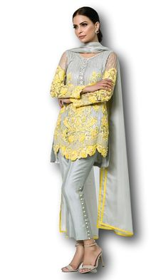 Set on a base of ash grey cotton net, this three piece ensemble features canary yellow embroidery with crystal embellishment and cutwork at the bottom. Comes with ash grey trousers in pure raw silk with crystal buttons and a net dupatta. Pakistani Fashion Casual, Pakistani Dresses Casual, Pakistani Dress Design, Pakistani Suits, Pakistani Bridal, Salwar Designs, Kurti Designs Party Wear, Dress Neck Designs, Designs For Dresses