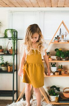 Boho girly outfit, so cute and so spring! Flower child baby girl in minimalist layered yellow outfit. Pinafore dress in mustard made from organic cotton for healthy sustainable living. Little sun dress perfect for playing outdoors or inside. Find at Noble Carriage by Gray Label.