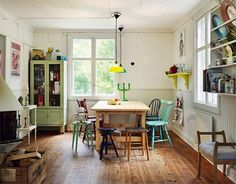 Swedish journalist & TV-presenter Ann Söderlund's summer country house (via Elle Interiör) vintage swedish Scandinavian cottage/home design...colorful amd cozy and fun with beautiful hardwood floors and beautiful, charming period details. Mismatched flea market chair style around a wood table and a cute green hutch for storage as we all know, in the US&EUROPE,  old houses have very few closets