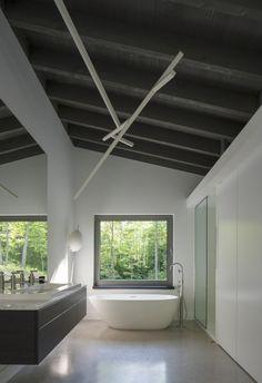 Bromont House / Paul Bernier Architecte  surprising placement of bathtub in kitchen/living area reminiscent of times past - pre hot water...