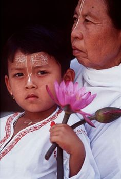 A prayer is inscribed in sandalwood paste on the forehead of a young Vaishnavite boy who holds a delicate lotus flower in his hand as an offering to the temple. In many religions, the lotus is a symbol of beauty, grace, divine peace and detachment from the earthly shackles of greed, anger, lust, passion, jealousy and ego. Growing out of muddy water to blossom into a lovely flower, the lotus symbolizes the potential in all beings to grow beyond sinful mortal foibles into enlightened beings
