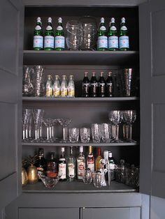 Masculine charcoal gray built-in bar cabinet lined with glassware and a variety of liquors.