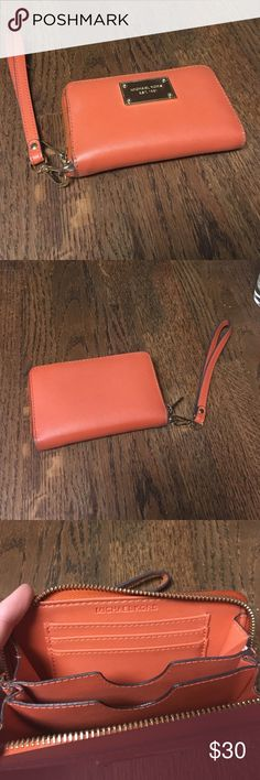 Authentic Michael Kors wallet Orange authentic Michael kors wallet! Has removable wristlet strap that comes with it. Has a few scratches on the metal plate and some wear you can see in the last picture. Make me an offer! Michael Kors Bags Wallets