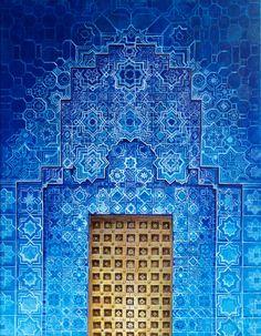 Gold Moroccan door on ornate blue building. Patterns, detail, cells.