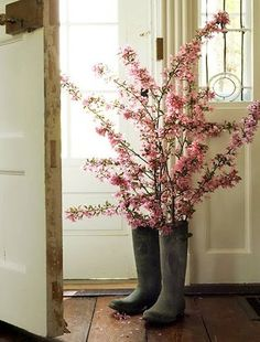 """I've done this every year for the past 3-4 yrs. Thrifted adult rain boots/muckers and faux flowering branches. Children's boots work well for the smaller bouquets of flowers. {brings to mind~""""April showers bring May flowers.""""} :)"""