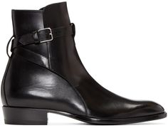 Ankle-high buffed leather boots in black. Almond toe. Wraparound strap featuring adjustable pin-buckle fastening at ankle. Grosgrain pull-tab at heel collar. Tonal leather sole. Silver-tone hardware. Tonal stitching.