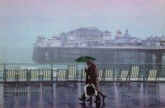 'Dirty Weekend' by local artist Philip Dunn - a couple walking along Brighton esplanade on a rainy day with the Palace Pier in the background