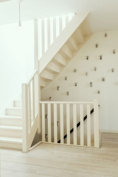 Elisah aka Interior Junkie has an all white hallway with one wall featuring house shaped decorations.   MADE.COM/Unboxed