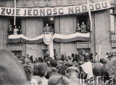 1945, Polska.  Prawdopodobnie Ziemie Odzyskane, tłum zgromadzony na wiecu. Balkon budynku, z którego jest wygłaszane przemówienie, jest ozdobiony biało-czerwoną flagą i godłem - Orłem bez korony, wyżej wisi hasło: