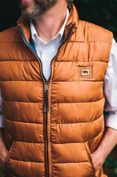 This men's vest has a rich texture from the light wax coating. (Shown here in rusty orange.) A quality micro puff men's vest, perfect for layering with an oxford or flannel shirt, jeans and boots. Also available in gray, brick red, or copper.
