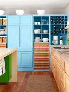 ~Colorful Charm Salvaged Cabinets~  All of the kitchen cabinets were found at a Habitat for Humanity ReStore, which sells new and gently used building materials to generate funds for low-income housing. Although the cabinets were in different styles, the mismatched set was unified with blue paint. To hide inconsistencies, you can also add molding at the top or bottom of the cabinets.