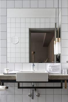 Brochner Boutique Hotels // Hotel SP34, Copenhagen // white tiles; mirror; concrete vanity; vanity towel rail