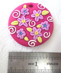 Polymer clay pendant, handmade with applique technique, one of a kind. Vibrant pink, with light purple flowers with blue and yellow centers, apple green leaves and white swirls. By Lis Shteindel.