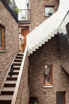 ~Mirrored walls and projecting staircases create optical illusions inside the brick-lined atrium of this apartment complex in Ghent, Belgium, by local office Atelier Vens Vanbelle. Architecture Résidentielle, Contemporary Architecture, Timber Windows, Concrete Stairs, Brickwork, Apartment Design, Stairways, Interior And Exterior, Interior Design