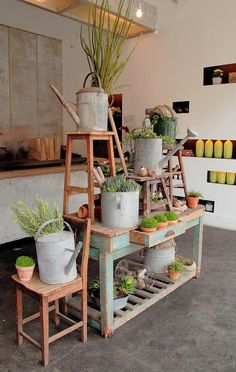 """Example of vertical display and a use for old tools, such as the watering cans, as containers.  For spring it creates a """"gardening"""" atmosphere, and clears out our garages."""