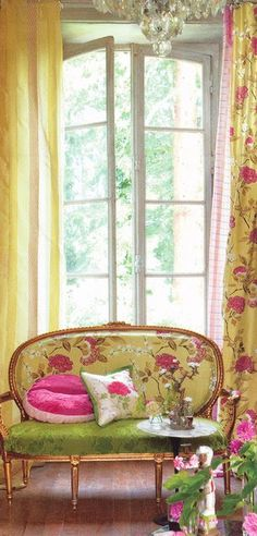 Bright 'n Pretty tea area: green, pink, and yellow floral settee, glass doors that open on garden, yellow floral curtains, chandelier floats above yet anchors the area.