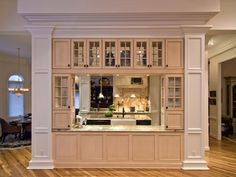 Molded columns flank the pass-through hutch, which houses dishes, silverware, small appliances, a wine cooler and an ice machine.