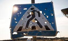Słońce świeci przez dziury w znaku drogowym, które powstały w wyniku ostrzału Doniecka, 25 lutego 2015 roku