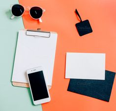 Creative flat lay of workspace desk with smartphone, clipboard, envelope, tag and sunglasses on minimal color background
