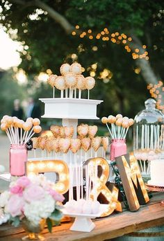 A pie-pop dessert stand with letter marquee lights and assorted cake pops.