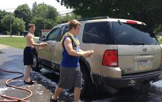 Pleasant Valley High School wrestlers Jason Jacobi, left, and Garrett Gouger, right, lather up an SUV during a car-wash fundraiser for their wrestling program.