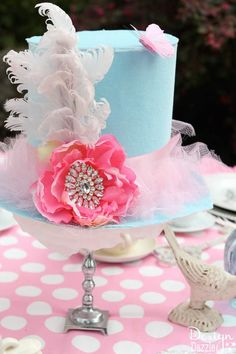 Vintage Glam Alice In Wonderland Party: Top hat centerpiece made from poster board and fabric with a silver colored candlestick that was used for the base. Feather, a jewel and flower embellishments were added with a glue gun.