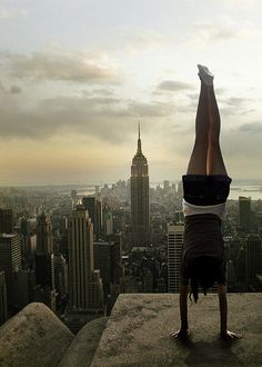 girl standing on her hands on the rooftop in front of the Empire States building - New York City