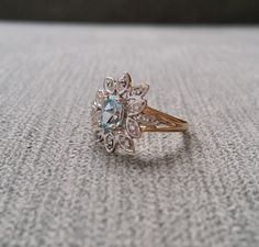 This Gorgeous 1930s Diamond Ring features an Antique White and Yellow 9K Gold Setting. Set with a .50 Carat Natural Aquamarine and 0.06 carats of