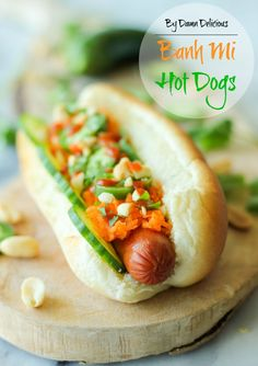 Banh Mi Hot Dogs -  These hot dogs have a banh mi twist, loaded with pickled carrots, jalapeños, cucumbers, cilantro, crushed peanuts and Sr...