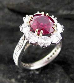 This platinum ring features a stunning 4.09ct ruby set with 18k yellow gold prongs surrounded by 8 diamonds This would be really nice!! Maybe shed like;)
