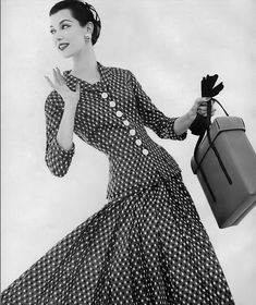 1955 Barbara Mullen in willowy dress and jacket of black, toast and white silk shantung, the dress is short-sleeved with deep swaying pleats, by Benham.