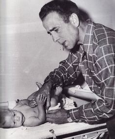 Tough guy HUMPHREY BOGART changing his son Stephen's diaper