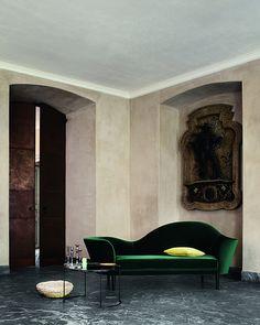 Les lignes courbes et le velours vert bouteille du canapé donnent de la chaleur à une pièce presque nue, minérale, aux murs beiges, au sol gris.