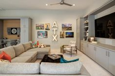 Marquee letters and photos add to the fun vibe of this family room. A large sectional makes sure everyone has a prime view for movie and game nights. games for family Game Room Kids, Game Room Basement, Basement Family Rooms, Garage Playroom, Game Room Design, Family Room Design, Family Home Games, Pool Table Room, Game Room Decor