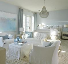 White and blue bedroom sitting area boasts a white tufted settee facing a white slipcovered skirted ottoman as coffee table topped with an acrylic tray flanked by white slipcovered chairs illuminated by a gray beaded chandelier.