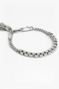 <ul> <li> Box chain and cable chain bracelet with two safety pin detail</li> <li> Chain tassel</li> <li> Lopster clasp</li> </ul>