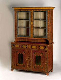 """Realized Price: $29250 Rare Somerset County, Pennsylvania painted pine wall cupboard, ca. 1835, in two parts, the upper section with two 6-light doors over a lower section with 2 drawers and 2 sunken panel doors, suppported by bracket feet, retaining its original vibrant and unique decorated surface, 84"""" h., 51"""" w., 21"""" d."""