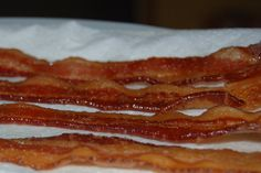 Cooking bacon in the oven - easy and less mess!   1. Line a cookie sheet with foil.  2. Place thick-sliced bacon in one layer on the sheet. Do not overlap slices.  3. Turn oven to 400 degrees (don't preheat). Put the bacon in the oven.  4. Check it after 15 minutes, but it might take closer to 20 minutes. (Can cook on rack in the pan so it doesn't cook in the grease)