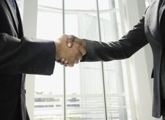 Two businessmen shaking hands - Sarah Fix Photography Inc/Getty Images