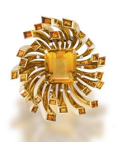 A retro citrine and diamond brooch, circa 1940 designed as a stylized flowerhead, centering a cut cornered rectangular-cut citrine, extending polished gold petals, each enhanced by a vari-cut citrine, further enhanced by single-cut diamonds; gross weight approximately: 68.2 grams; length 2 1/2in.