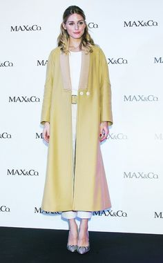 Olivia Palermo wears a paneled camel coat with a white top, pants, and pointed-toe flats