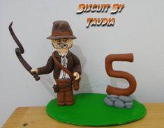 Topo de bolo modelado em porcelana fria, com o personagem Indiana Jones Lego.  O que difere este topo do modelo anterior são as pedras onde se fixa a idade da criança.  Consulte-nos pois podemos personalizar este topo de muitas maneiras.  No ato do fechamento, favor informar o cep para calculo do frete, que é por conta do cliente, obrigada. R$ 50,00