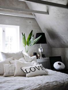 屋根裏の隠れ家みたいな、とっておきのベッドルーム。光を反射しすぎないトーンでまとめた室内は、白い枠の大きな窓からの採光も、柔らかに取り込みます。