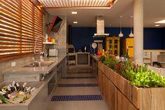 Cozinha gourmet com horta de temperos de um lado. Embaixo o armário com acessórios para mexer na horta...