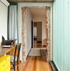 A passarela liga o quarto do casal ao closet, passando pelo escritório. A arquiteta Mariana Andersen pediu para o pedreiro não reenquadrar o vão, para mostrar a intervenção. Há também a opção de isolar a área de dormir com uma cortina