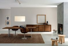 wood tone and exposed concrete in the dining room, contain a wooden dining table with two wooden dining chairs on brown rug, white drum pendant lamp, wooden sideboard, a fireplace and two wooden stools
