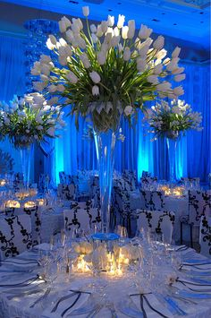 Tulips spilling out of a sky high vase is oh so chic, like the spilling out look maybe not tulips though...could be  beautiful Christmas/Hannukah event decor