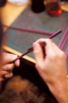 A craftsman works on a set of red violet-colored chopsticks, hand-made at the Kyoto Chopstick Workshop.