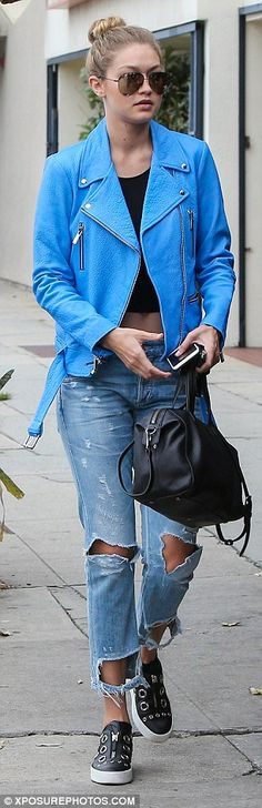 Blue belle: Gigi, 20, looked casual yet stylish in ripped jeans, a crop top and statement blue leather jacket